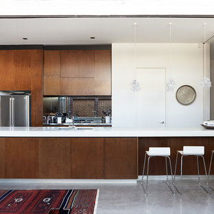 This is an example of a large contemporary kitchen in Sydney with quartz benchtops, stainless steel appliances, concrete floors, flat-panel cabinets, dark wood cabinets, a peninsula and an undermount sink.