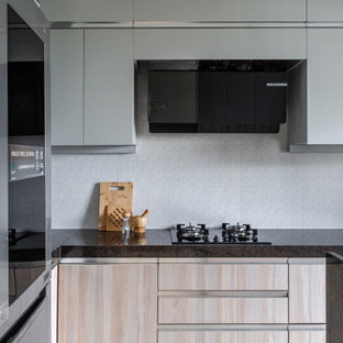 На фото: угловая кухня среднего размера в современном стиле с плоскими фасадами, бежевыми фасадами, белым фартуком, фартуком из керамогранитной плитки, техникой под мебельный фасад, полом из терраццо, бежевым полом и коричневой столешницей