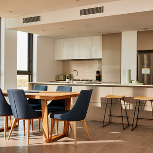 This is an example of a large contemporary galley eat-in kitchen in Sydney with an undermount sink, grey cabinets, quartz benchtops, white splashback, ceramic splashback, stainless steel appliances, ceramic floors, with island, white benchtop, flat-panel cabinets and brown floor.