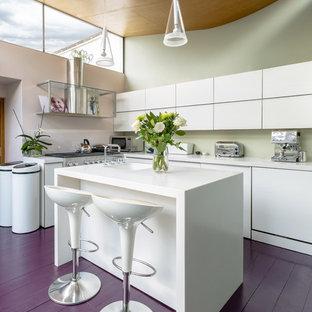 Идея дизайна: угловая кухня-гостиная среднего размера в современном стиле с монолитной раковиной, плоскими фасадами, белыми фасадами, столешницей из кварцита, фартуком из стекла, техникой из нержавеющей стали, островом, деревянным полом и фиолетовым полом