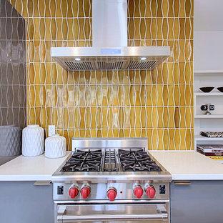 フェニックスの中くらいのミッドセンチュリースタイルのおしゃれなキッチン (アンダーカウンターシンク、フラットパネル扉のキャビネット、グレーのキャビネット、クオーツストーンカウンター、黄色いキッチンパネル、セラミックタイルのキッチンパネル、シルバーの調理設備、コンクリートの床) の写真