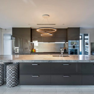 Photo of a large contemporary galley eat-in kitchen in Adelaide with a drop-in sink, brown cabinets, green splashback, glass tile splashback, stainless steel appliances, porcelain floors, with island, louvered cabinets, marble benchtops, white floor and grey benchtop.