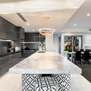 Idee per una grande cucina design con lavello da incasso, ante marroni, top in quarzo composito, paraspruzzi verde, paraspruzzi con piastrelle di vetro, elettrodomestici in acciaio inossidabile, pavimento in gres porcellanato, isola, ante a persiana, pavimento bianco e top grigio