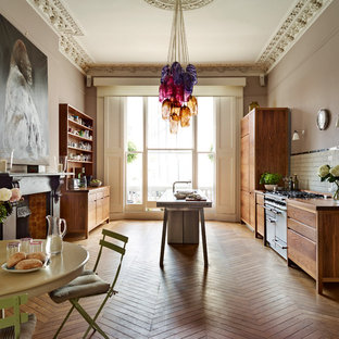 Inspiration for an eclectic galley eat-in kitchen in Other with flat-panel cabinets, medium wood cabinets, wood benchtops, white splashback, subway tile splashback, stainless steel appliances, medium hardwood floors, with island and brown floor.