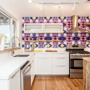 Mid-sized danish l-shaped light wood floor eat-in kitchen photo in Austin with flat-panel cabinets, white cabinets, multicolored backsplash, stainless steel appliances and an island