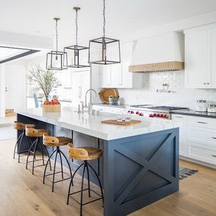 Inspiration for a beach style galley light wood floor and beige floor kitchen remodel in Los Angeles with a farmhouse sink, shaker cabinets, white cabinets, white backsplash, paneled appliances, an island and black countertops
