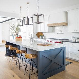 На фото: параллельная кухня в морском стиле с раковиной в стиле кантри, фасадами в стиле шейкер, белыми фасадами, белым фартуком, техникой под мебельный фасад, островом, черной столешницей, светлым паркетным полом и бежевым полом с
