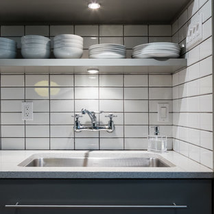 Mid-sized midcentury modern eat-in kitchen designs - Mid-sized 1960s galley ceramic floor eat-in kitchen photo in Birmingham with an undermount sink, flat-panel cabinets, gray cabinets, concrete countertops, white backsplash, ceramic backsplash, stainless steel appliances and no island