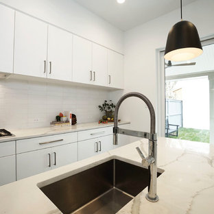 Photo of a small modern l-shaped separate kitchen in Richmond with an undermount sink, flat-panel cabinets, white cabinets, quartz benchtops, white splashback, ceramic splashback, stainless steel appliances, ceramic floors, with island, black floor and white benchtop.