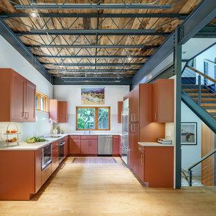 Foto på ett mellanstort industriellt grå u-kök, med en undermonterad diskho, släta luckor, orange skåp, bänkskiva i kvarts, grått stänkskydd, stänkskydd i sten, rostfria vitvaror, ljust trägolv och beiget golv