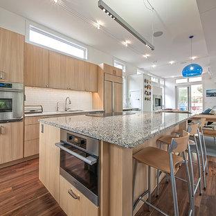 Zweizeilige, Mittelgroße Moderne Wohnküche mit Waschbecken, flächenbündigen Schrankfronten, hellen Holzschränken, Arbeitsplatte aus Terrazzo, Küchenrückwand in Weiß, Rückwand aus Glasfliesen, Küchengeräten aus Edelstahl, braunem Holzboden und Kücheninsel in Denver