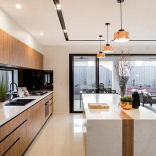 ブリスベンの中サイズのモダンスタイルのおしゃれなキッチン (ダブルシンク、落し込みパネル扉のキャビネット、中間色木目調キャビネット、人工大理石カウンター、オレンジのキッチンパネル、ミラータイルのキッチンパネル、パネルと同色の調理設備、セラミックタイルの床、ベージュの床) の写真