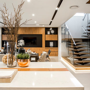 This is an example of a mid-sized modern galley open plan kitchen in Brisbane with recessed-panel cabinets, medium wood cabinets, solid surface benchtops, orange splashback, mirror splashback, panelled appliances, ceramic floors, with island and beige floor.