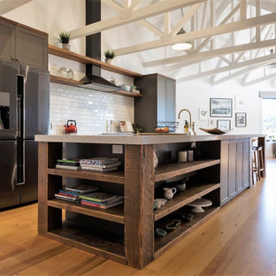This is an example of an expansive country single-wall open plan kitchen in Auckland with dark wood cabinets, concrete benchtops, ceramic splashback, stainless steel appliances, medium hardwood floors, with island and yellow floor.