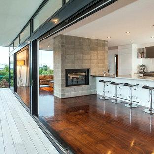 Immagine di una cucina minimal di medie dimensioni con top in acciaio inossidabile, paraspruzzi bianco, paraspruzzi con lastra di vetro, elettrodomestici in acciaio inossidabile e pavimento in compensato
