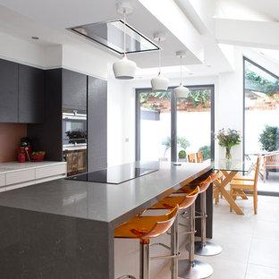 Mittelgroße, Zweizeilige Moderne Wohnküche mit flächenbündigen Schrankfronten, Kücheninsel, Unterbauwaschbecken, schwarzen Schränken, Küchenrückwand in Rot, Glasrückwand, Elektrogeräten mit Frontblende und beigem Boden in London