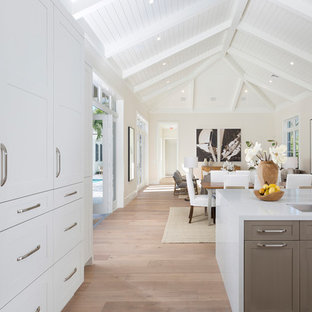 Photo of an expansive tropical galley open plan kitchen in Miami with a double-bowl sink, recessed-panel cabinets, grey cabinets, wood benchtops, stainless steel appliances, light hardwood floors, with island, beige floor and white benchtop.