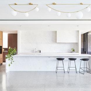 Inspiration for a modern kitchen in Melbourne with flat-panel cabinets, light wood cabinets, white splashback, panelled appliances, concrete floors, an island, grey floor and white benchtop.