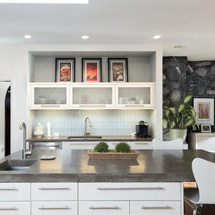 バーミングハムの広いミッドセンチュリースタイルのおしゃれなキッチン (アンダーカウンターシンク、フラットパネル扉のキャビネット、白いキャビネット、コンクリートカウンター、青いキッチンパネル、ガラスタイルのキッチンパネル、シルバーの調理設備、無垢フローリング) の写真