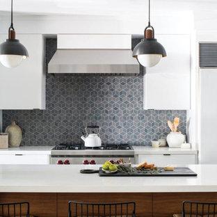 ロサンゼルスの大きいビーチスタイルのおしゃれなキッチン (アンダーカウンターシンク、フラットパネル扉のキャビネット、白いキャビネット、クオーツストーンカウンター、青いキッチンパネル、セメントタイルのキッチンパネル、シルバーの調理設備、濃色無垢フローリング、黒い床、白いキッチンカウンター) の写真