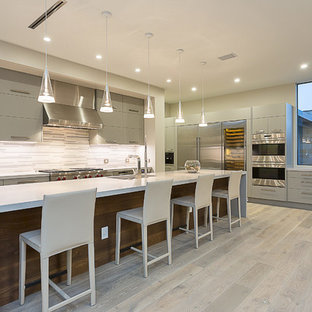 Kitchen - contemporary l-shaped light wood floor kitchen idea in Austin with an undermount sink, flat-panel cabinets, gray cabinets, white backsplash, stainless steel appliances and an island