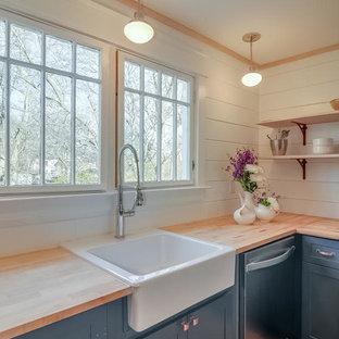 ナッシュビルの中サイズのシャビーシック調のおしゃれなキッチン (エプロンフロントシンク、シェーカースタイル扉のキャビネット、青いキャビネット、木材カウンター、白いキッチンパネル、シルバーの調理設備の、淡色無垢フローリング) の写真
