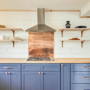 Diseño de cocina comedor en U, romántica, de tamaño medio, con fregadero sobremueble, armarios estilo shaker, puertas de armario azules, encimera de madera, salpicadero blanco, electrodomésticos de acero inoxidable y suelo de madera clara