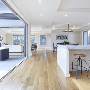 Design ideas for a large traditional single-wall kitchen pantry in Melbourne with a double-bowl sink, louvered cabinets, quartz benchtops, white splashback, stone tile splashback, white appliances, light hardwood floors and with island.