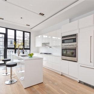 ニューヨークの広いモダンスタイルのおしゃれなキッチン (フラットパネル扉のキャビネット、白いキャビネット、ドロップインシンク、大理石カウンター、白いキッチンパネル、シルバーの調理設備、淡色無垢フローリング、茶色い床) の写真