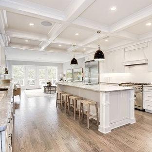 ワシントンD.C.の中くらいのトランジショナルスタイルのおしゃれなキッチン (アンダーカウンターシンク、シェーカースタイル扉のキャビネット、白いキャビネット、御影石カウンター、白いキッチンパネル、セラミックタイルのキッチンパネル、シルバーの調理設備、無垢フローリング、茶色い床、ベージュのキッチンカウンター) の写真