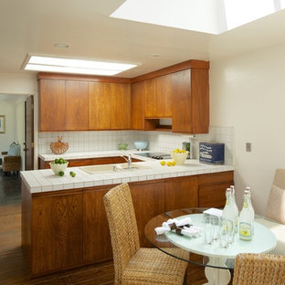 This is an example of a midcentury eat-in kitchen in San Francisco with a drop-in sink, flat-panel cabinets, medium wood cabinets, tile benchtops, white splashback and white appliances.