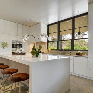 Moderne Küche in L-Form mit flächenbündigen Schrankfronten, weißen Schränken, Küchenrückwand in Beige, Rückwand aus Stein, Teppichboden und Kücheninsel in Austin