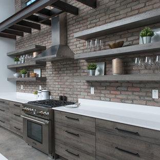 フェニックスの中くらいのインダストリアルスタイルのおしゃれなキッチン (アンダーカウンターシンク、フラットパネル扉のキャビネット、中間色木目調キャビネット、珪岩カウンター、赤いキッチンパネル、レンガのキッチンパネル、シルバーの調理設備、コンクリートの床、グレーの床、白いキッチンカウンター) の写真
