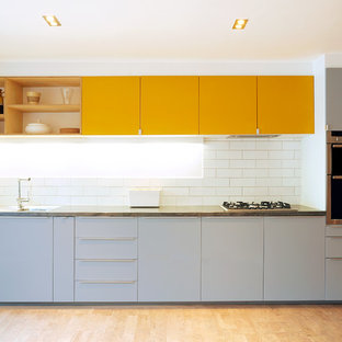 Mid-sized contemporary open concept kitchen photos - Open concept kitchen - mid-sized contemporary single-wall open concept kitchen idea in London with flat-panel cabinets, yellow cabinets, concrete countertops, white backsplash, porcelain backsplash and stainless steel appliances