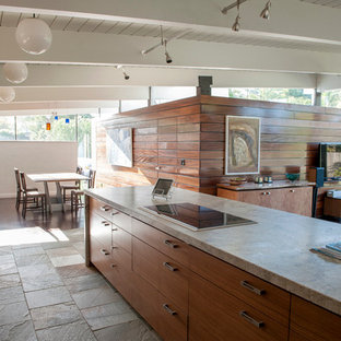 Large contemporary l-shaped open plan kitchen in San Francisco with a double-bowl sink, flat-panel cabinets, medium wood cabinets, granite benchtops, multi-coloured splashback, stone tile splashback, stainless steel appliances, slate floors, with island and grey floor.