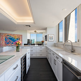 Contemporary kitchen ideas - Inspiration for a contemporary l-shaped black floor kitchen remodel in Other with an undermount sink, recessed-panel cabinets, white cabinets, stone slab backsplash, an island and white countertops