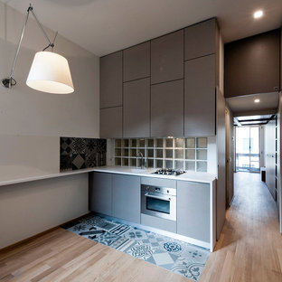 This is an example of a small modern single-wall eat-in kitchen in Milan with an integrated sink, flat-panel cabinets, grey cabinets, solid surface benchtops, white splashback, glass sheet splashback, stainless steel appliances and ceramic floors.