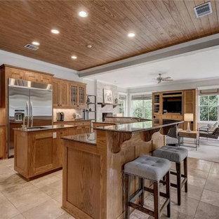 オースティンの広いサンタフェスタイルのおしゃれなキッチン (アンダーカウンターシンク、レイズドパネル扉のキャビネット、中間色木目調キャビネット、御影石カウンター、ベージュキッチンパネル、石タイルのキッチンパネル、シルバーの調理設備、トラバーチンの床、白い床、茶色いキッチンカウンター、板張り天井) の写真