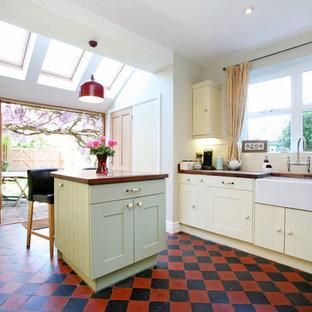 Geschlossene Klassische Küche mit Landhausspüle, gelben Schränken, Arbeitsplatte aus Holz, buntem Boden und brauner Arbeitsplatte in London