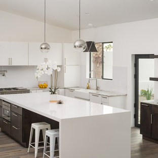 Contemporary kitchen ideas - Kitchen - contemporary l-shaped light wood floor and beige floor kitchen idea in Phoenix with flat-panel cabinets, an island, a farmhouse sink, white cabinets, white backsplash, glass sheet backsplash and stainless steel appliances