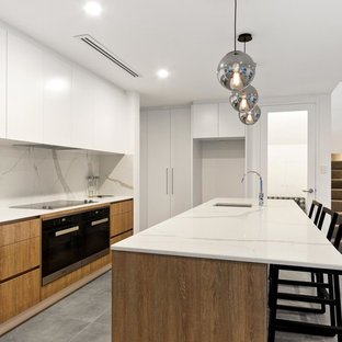Design ideas for a mid-sized contemporary galley open plan kitchen in Perth with flat-panel cabinets, marble benchtops, white splashback, marble splashback, black appliances, ceramic floors, an island, grey floor, white benchtop, an undermount sink and medium wood cabinets.