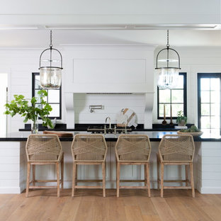 Country single-wall kitchen in Phoenix with shaker cabinets, white cabinets, soapstone benchtops, with island, black benchtop, white splashback, timber splashback, medium hardwood floors and brown floor.