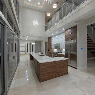 マイアミの中サイズのモダンスタイルのおしゃれなキッチン (アンダーカウンターシンク、フラットパネル扉のキャビネット、中間色木目調キャビネット、大理石カウンター、白いキッチンパネル、石スラブのキッチンパネル、シルバーの調理設備の、大理石の床) の写真