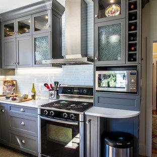 Пример оригинального дизайна интерьера: маленькая отдельная, угловая кухня в современном стиле с раковиной в стиле кантри, фасадами в стиле шейкер, серыми фасадами, столешницей из кварцевого композита, белым фартуком, фартуком из стеклянной плитки, техникой из нержавеющей стали, пробковым полом и островом