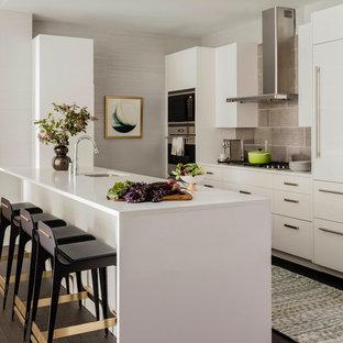 Foto på ett mellanstort funkis vit parallellkök, med en undermonterad diskho, släta luckor, vita skåp, bänkskiva i kvarts, rostfria vitvaror, mörkt trägolv, en halv köksö, brunt golv och grått stänkskydd