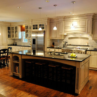 Large traditional eat-in kitchen appliance - Eat-in kitchen - large traditional l-shaped medium tone wood floor eat-in kitchen idea in Charlotte with raised-panel cabinets, beige backsplash, an island, an undermount sink, subway tile backsplash, stainless steel appliances and white cabinets