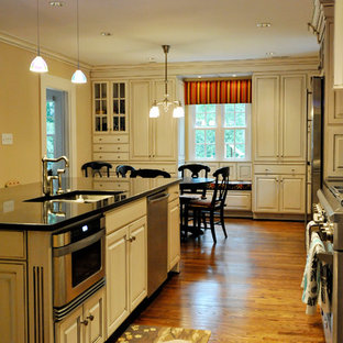 Large traditional eat-in kitchen ideas - Large elegant l-shaped medium tone wood floor eat-in kitchen photo in Charlotte with an undermount sink, raised-panel cabinets, white cabinets, beige backsplash, subway tile backsplash, stainless steel appliances and an island
