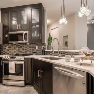 Photo of a small contemporary kitchen in Denver with a single-bowl sink, shaker cabinets, black cabinets, quartz benchtops, grey splashback, glass tile splashback, stainless steel appliances, vinyl floors, no island, grey floor and white benchtop.