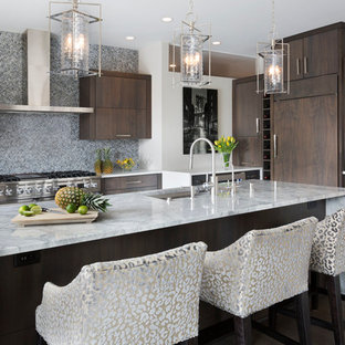 Design ideas for an expansive contemporary l-shaped open plan kitchen in Milwaukee with an undermount sink, flat-panel cabinets, dark wood cabinets, marble benchtops, grey splashback, glass tile splashback, stainless steel appliances, dark hardwood floors, with island, brown floor and white benchtop.