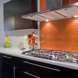 ニューアークの広いモダンスタイルのおしゃれなキッチン (シングルシンク、フラットパネル扉のキャビネット、濃色木目調キャビネット、御影石カウンター、オレンジのキッチンパネル、セラミックタイルのキッチンパネル、シルバーの調理設備、磁器タイルの床、アイランドなし、グレーの床) の写真